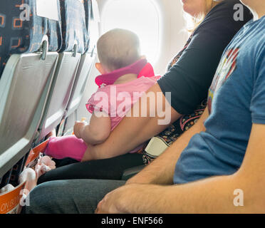 A baby on its parents lap on a passenger plane - Stock Image