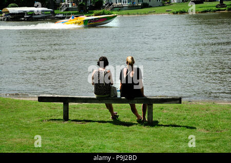 Two women sitting on park bench at waters edge watching boats pass by. - Stock Image