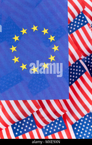 EU flag with mass of small US Stars and Stripes flags - metaphor of Trump trade tariffs on imported EU goods, and US EU trade war / barriers. - Stock Image