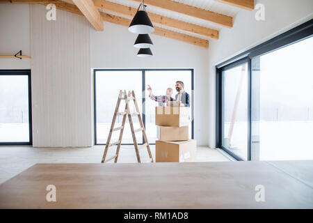 A senior man helping his son with furnishing new house, a new home concept. - Stock Image
