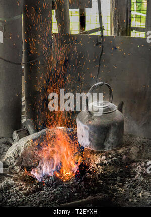 A tin kettle hangs over a fire to make green tea, Shan hills, Myanmar. - Stock Image