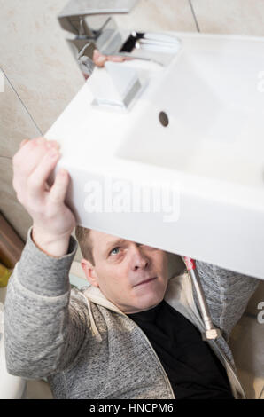Young man attempting Do It Yourself (DIY) plumbing at home under a sink fitting a new tap with a look of concentration - Stock Image