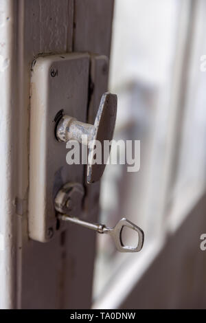 Old door with vintage door knob and key - Stock Image
