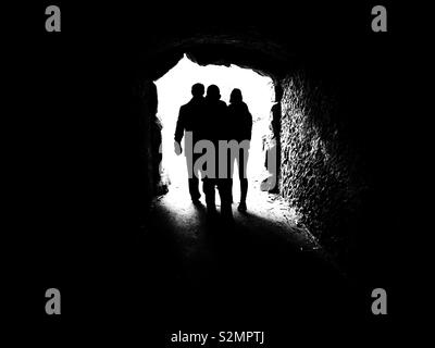 Silhouettes of 3 people walking out of a dark tunnel - Stock Image