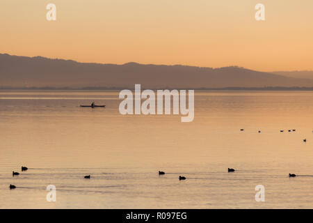Beautiful view of a lake at sunset, with orange tones, birds on water and a man on a canoe. - Stock Image