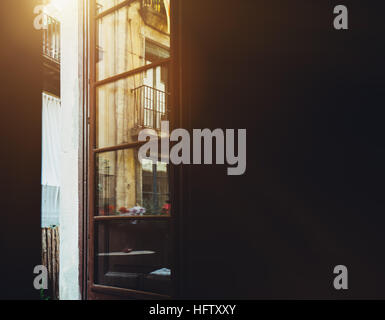 View from dark room to opened balcony door with reflections: facade of historical old residential house in Barcelona - Stock Image