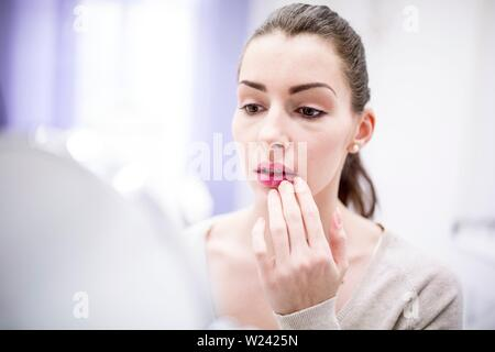 Woman looking at her lips in mirror. - Stock Image