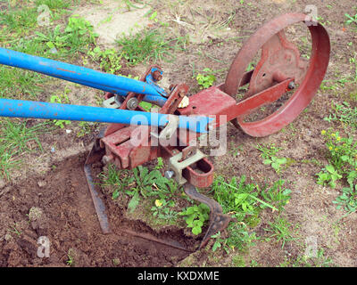 Tilling the soil with pushed by hands garden cultivator - Stock Image