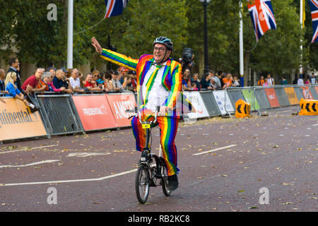 A man in a rainbow suit waving as he rides along The Mall with onlooking crowd, Brompton World Championships 2018, London, UK - Stock Image