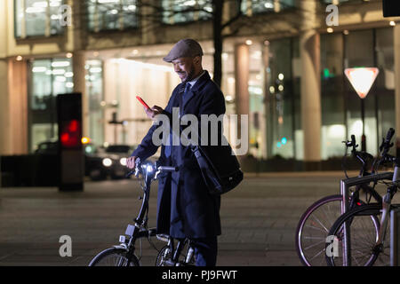 Businessman with smart phone and bicycle on urban street at night - Stock Image