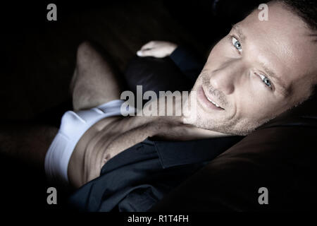 Portrait of a middle aged man sitting in leather armchair in his underwear and sixpack abs looking at camera - Stock Image