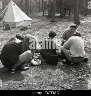1960s, historical, adventure scouts in the forest at an outdoor activity course perparing food - strips of meat for a stew?, England, UK. - Stock Image