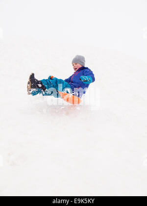 small laughing boy sledging fast down a steep hill in a cloud of snow - Stock Image