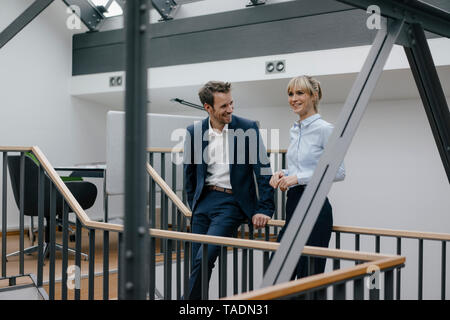 Businessman and woman standing in office building, discussing - Stock Image