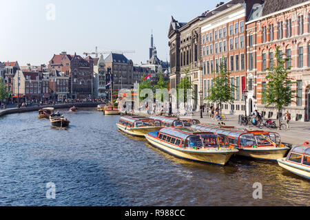 Tourist cruise boats and traditional Dutch buildings on the Rokin in Amsterdam, Netherlands - Stock Image