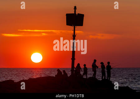 People stand on the jetty, some fishing, and watch the sunset at Menemsha Beach in Chilmark, Massachusetts on Martha's Vineyard. - Stock Image