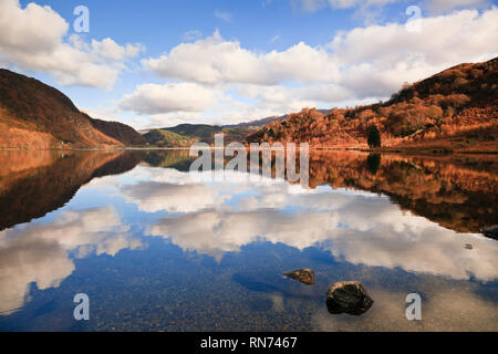 White cloud reflections in Llyn Dinas in the Nantgwynant valley in Snowdonia National Park in autumn. Beddgelert, Gwynedd, North Wales, UK, Britain - Stock Image