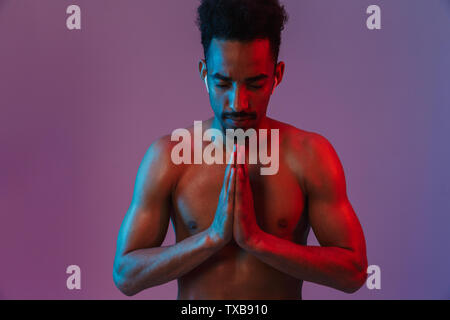 Portrait of calming shirtless african american man poising with earpods and hands in prayer isolated over violet background - Stock Image
