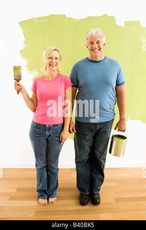 Portrait of happy adult couple standing in front of half painted wall with paint supplies American Gothic style - Stock Image
