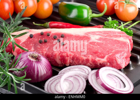 Barbecue steak ingredients on the grill, ready to prepare. - Stock Image