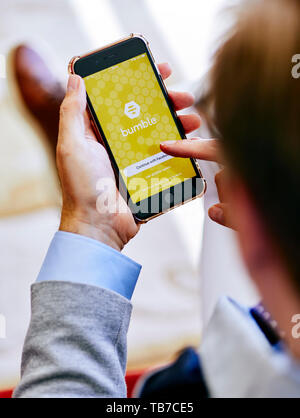 Close up of male using Bumble app on iPhone - Stock Image