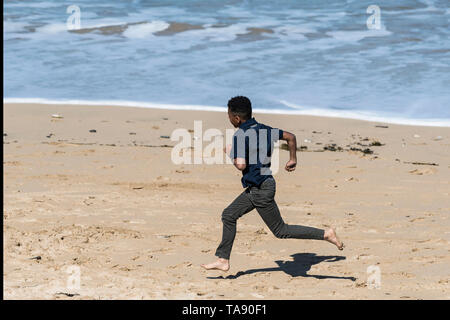 A young teenage boy running enthusiastically on a sunny day at Fistral Beach in Newquay in Cornwall. - Stock Image