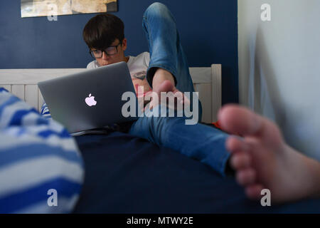 A teenage boy (AGE 14) lays on his bed with a mac book air laptop doing his homework fully clothed but with bare feet. - Stock Image