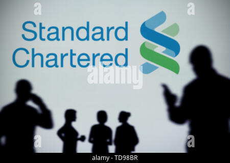 The Standard Chartered logo is seen on an LED screen in the background while a silhouetted person uses a smartphone (Editorial use only) - Stock Image