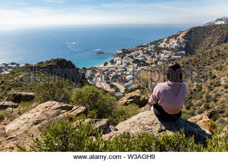 Beautiful woman sitting on a cliff with the mediterranean sea and small coast town in the background in Spain - Stock Image
