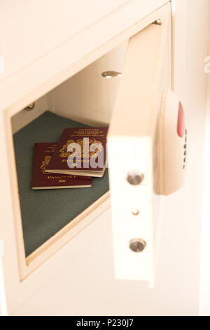 Two passports inside an open hotel room safe or strongbox. The safe has a keypad and an extra thick door for security. Its hidden in a  wardrobe - Stock Image