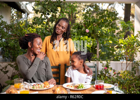 Three generations of women sitting at a lunch table - Stock Image