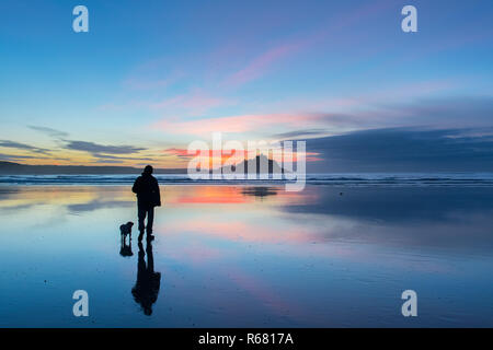 Man and his dog walking on the beach at Longrock at sunrise with St Michaels mount in the background - Stock Image