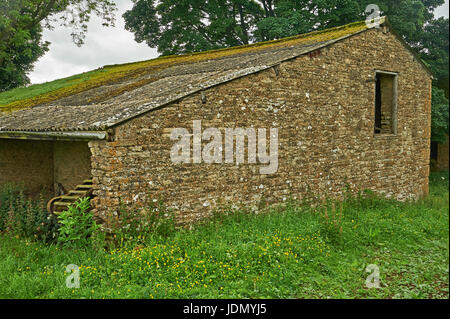 Stone barns in a valley high up on the Cotswold escarpment near the village of Cutsdean - Stock Image