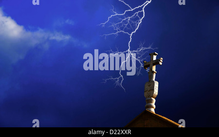 A close up of the cross on the top of a church, with a lightning on the background - Stock Image