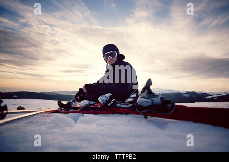 Portrait of skier sitting on snowy landscape against sky - Stock Image
