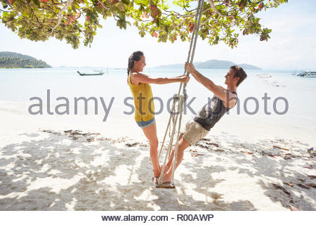 Young couple on beach swing - Stock Image