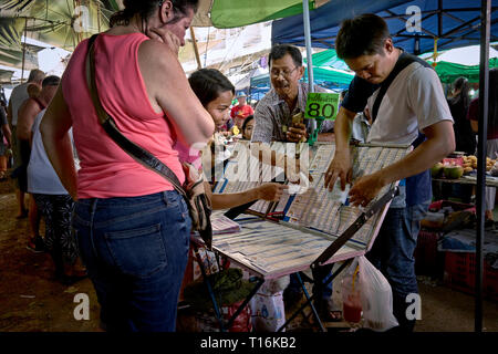 Thailand lottery. People buying lottery tickets from a Thai lottery ticket vendor. Southeast Asia - Stock Image