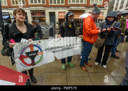 London, UK. 17th October 2018. People hold the DPAC (Disabled People Against Cuts) banner at the protest outside the Ministry of Housing, Communities and Local Government by residents living in tower blocks covered in Grenfell-style cladding, Fuel Poverty Action, and Grenfell campaigners demanding that the government make all tower-block homes safe and warm. Credit: Peter Marshall/Alamy Live News - Stock Image