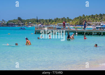 Swimmers oying the pristine waters of West Bay Beach in Roatan Honduras. - Stock Image
