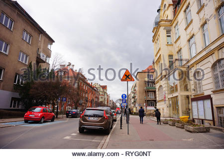 Poznan, Poland - March 8, 2019: Parked cars and people walking on a sidewalk with apartment building on the Slowackiego street. - Stock Image