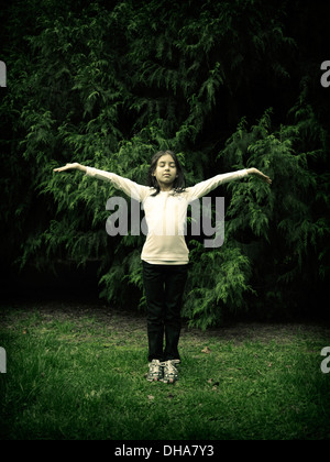 Girl, arms out, eyes closed, conifers - Stock Image