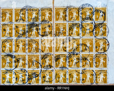 Multiple low value 2c Swiss 'William Tell' postage stamps used on parcel wrapping, 1921. - Stock Image