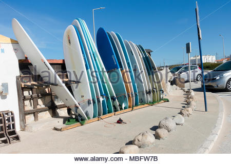 many surfboards in a line outside a surf school Baleal Peniche on the Portuguese Silver Coast - Stock Image