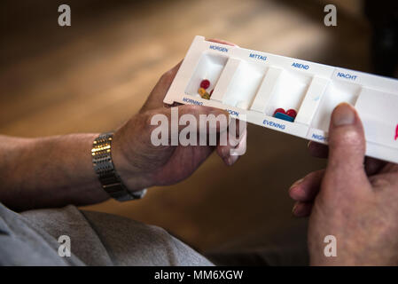 Close up of hands of senior man with tablet dispensers - Stock Image