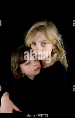 Two young sisters grieving and holding each other - Stock Image
