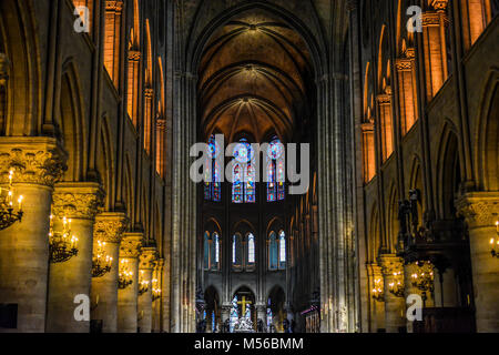 The beautiful, colorful and solemn interior of the Notre Dame Cathedral in Paris France with stained glass windows - Stock Image