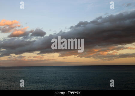 Colorful landscape with a stunning sunset located in Funchal, Madeira. The sky is colored with orange, gold and blue. - Stock Image