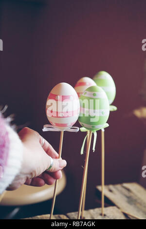 A beautiful close-up of 3 easter eggs on sticks over tables with a woman hand holding them and an amazing depth of field as background - Stock Image