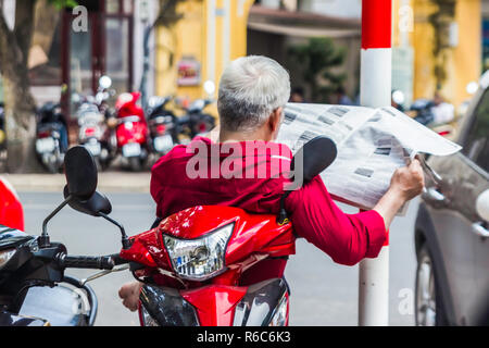 unrecognizable man in red shirt reads newspaper, sits on the scooter, empty street of Hanoi Vietnam, - Stock Image