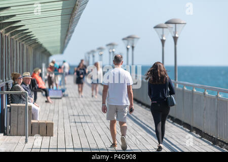 Bournemouth, UK. 22nd June 2018. UK sunny weather, adults walking down the pier in Boscombe beach in Bournemouth. Thomas Faull/Alamy Live News - Stock Image